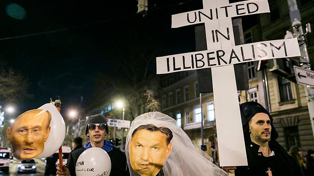 """""""מאוחדים בחוסר ליברליזם"""". מפגינים נגד אורבן ופוטין בבודפשט (צילום: EPA)"""