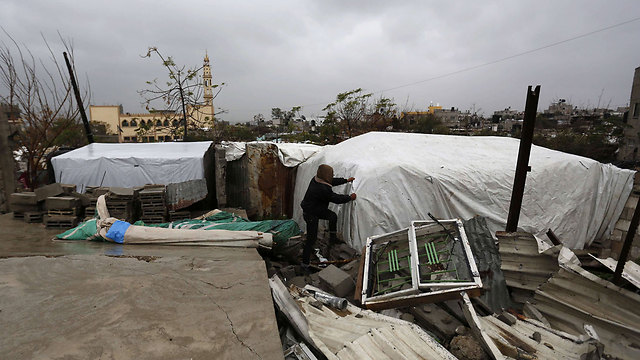 Rain-proofing a makeshift shelter in Gaza (Photo: AFP)