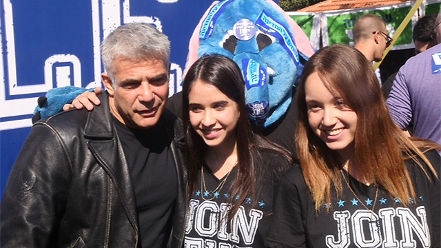 Lapid at the mock elections with two students (Photo: Motti Kimchi)
