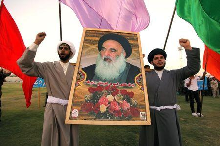 Shi'ite volunteers, who joined Iraqi army, carry picture of Grand Ayatollah Ali Sistani during a graduation ceremony after completing field training (Photo: Reuters) (Photo: Reuters)