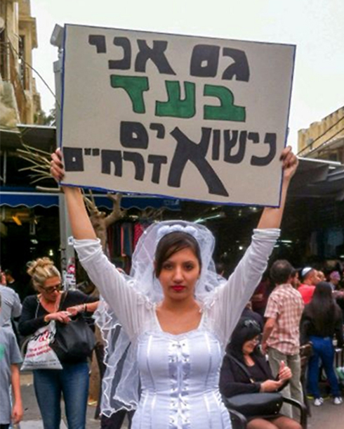 Woman dressed as bride holds sign reading 'I'm also in favor of civil marriage'