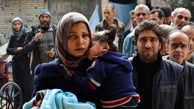Refugees wait in line for UN humanitarian aid at Yarmuk Refugee Camp in Syria (Photo: Reuters)