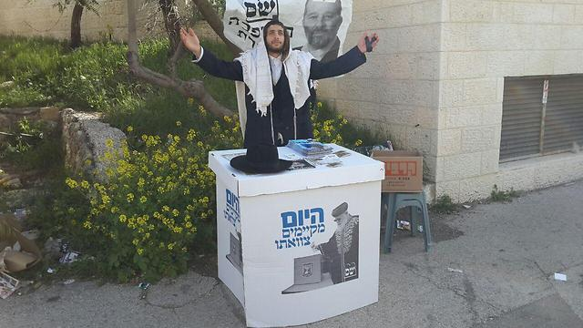 A Shas supporter engages in some last-minute campaigning in Jerusalem