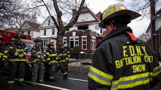 כבאים ליד הדירה שנשרפה. יותר מ-100 השתתפו בכיבוי השריפה (צילום: רויטרס) (צילום: רויטרס)