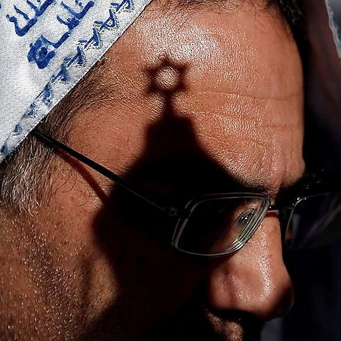 A star of David casts a shadow across a worshipper's face (Photo: AFP)