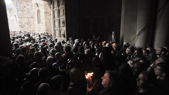 A Christian pilgrim holds up a candle as others gather at the church of the Holy Sepulcher (Photo: AP)