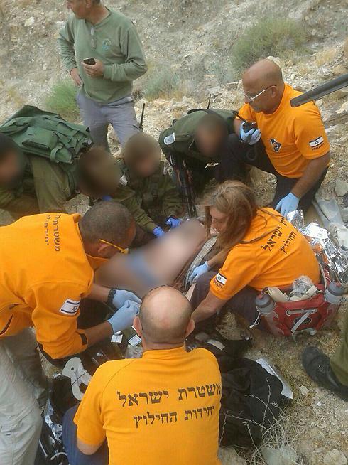 מתנדבי יחידת החילוץ מגילות מטפלים בנהג שהתהפך (צילום: יחידת חילוץ מגילות) (צילום: יחידת חילוץ מגילות)