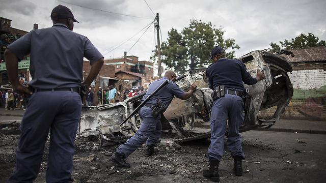 מפנים מכונית שהוצתה (צילום: AFP) (צילום: AFP)