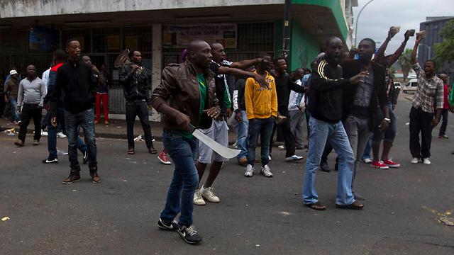 מהגרים יצאו לרחובות עם מאצ'טות כדי להתגונן מפני שונאי הזרים (צילום: רויטרס) (צילום: רויטרס)