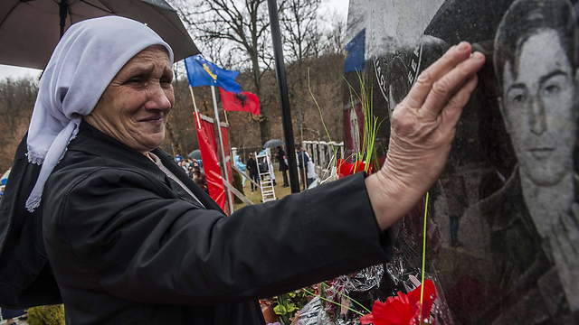אלבנית בקוסובו ליד קבר בנה שנהרג במלחמה (צילום: AFP)