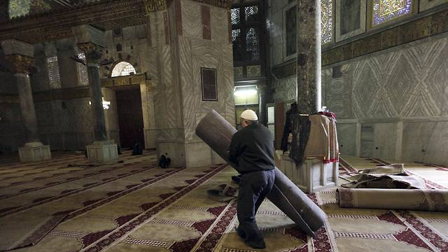 A worker carries new carpets at the Dome of the Rock shrine (Photo: AP)