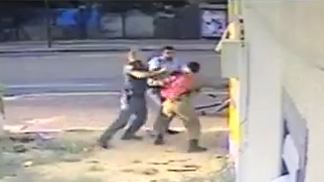 Police officers attacking an Israeli soldier of Ethiopian origin