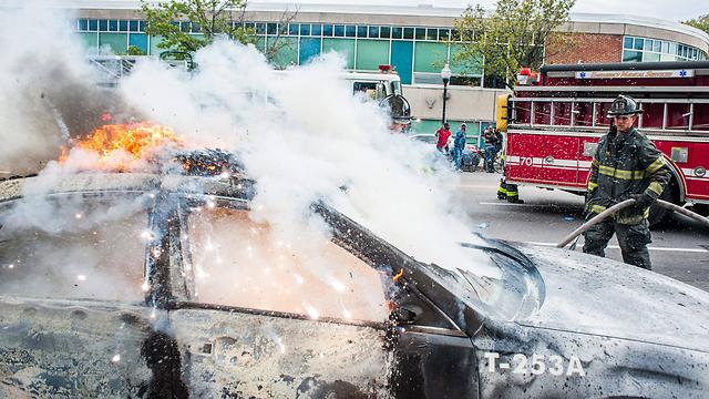 Firefighters extinguish burning car (Photo: EPA)