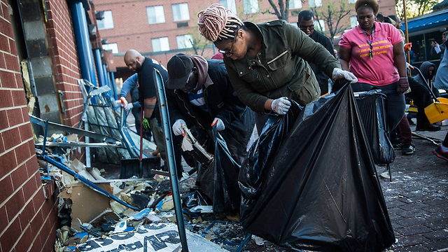 Volunteers cleaning up streets of Baltimore (Photo: AFP)