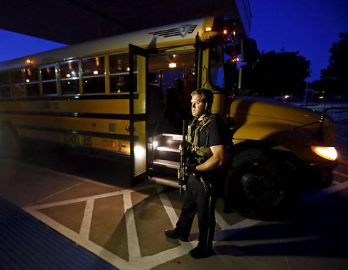 מאבטח לאוטובוס שהעביר את המשתתפים באירוע לבית ספר סמוך (צילום: רויטרס) (צילום: רויטרס)