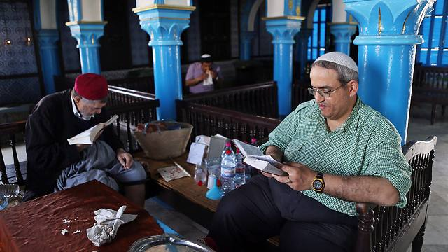 A Tunisian Rabbi and a Jewish man read the Torah inside the ancient Ghriba Synagogue (Photo: EPA)