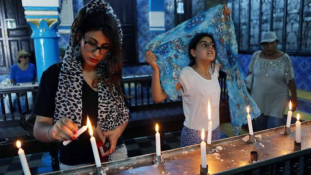 Visitors lighting a candle inside the ancient Ghriba Synagogue (Photo: EPA)