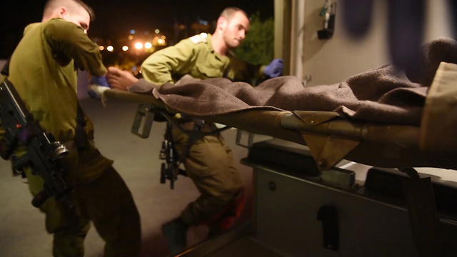 IDF soldiers rush the wounded from Syria to Israel (Photo: Eli Segal)