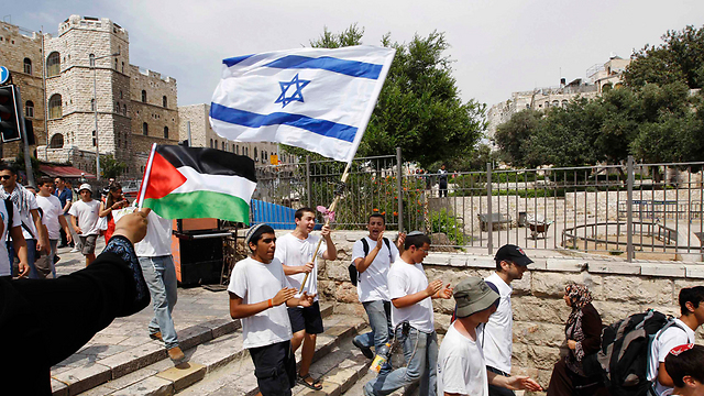 Woman waves Palestinian flag as Jewish boys march past (Photo: Reuters)