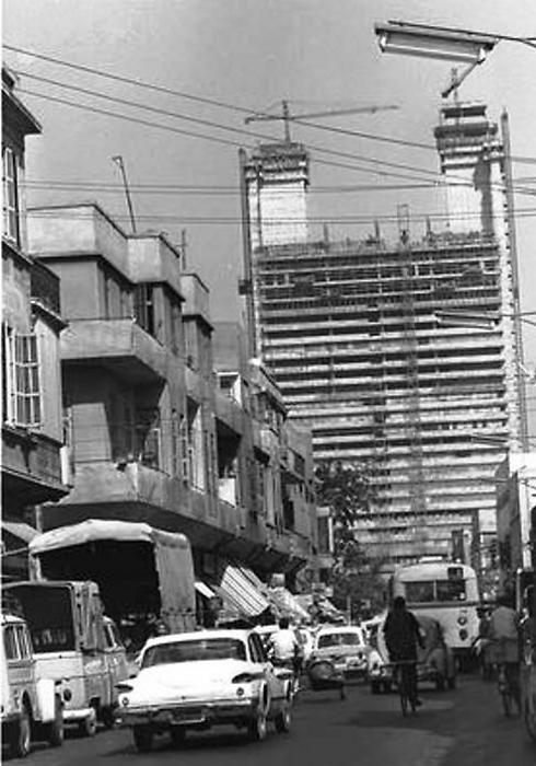 """תמונה נדירה זו מ-1964 מציגה את שיטת הבנייה המיוחדת של המגדל. ראשית נבנו שני צריחים בשני צידיו, ובהמשך נבנה החלק המרכזי כמעין גשרים, שכמובן נשענו על עמודים תומכים (צילום: כהן פריץ, לע""""מ)"""