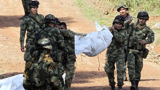 חיילים נושאים גופת חייל שנהרג בהתקפה של מורדים מארגון FARC (צילום: AFP,  EL TIEMPO)