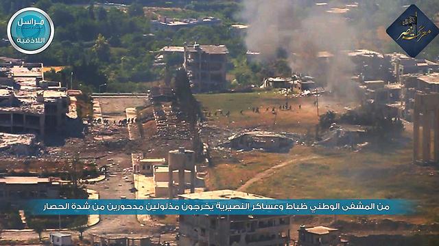 Assad soldiers flee from Jabhat al-Nusra's siege on the Jisr ash-Shugur hospital (Photo: Twitter)