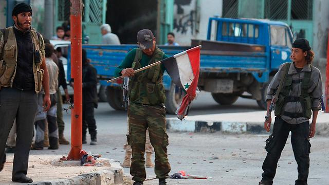 כוחות המורדים שורפים את דגל סוריה באריחא (צילום: רויטרס) (צילום: רויטרס)