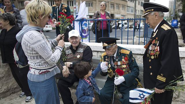 Russian Israeli World War II veterans who served as Russian soldiers from the Soviet Union are greeted by a child during a Victory in Europe Day parade in Jerusalem (Photo: EPA)