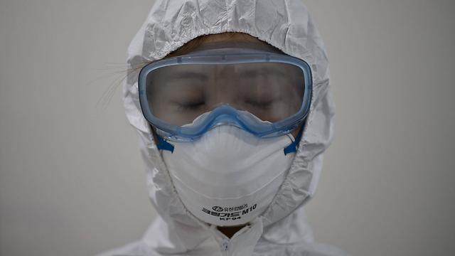 עובד בבית חולים בדרום-קוריאה. כל חולה המסתובב באופן חופשי מדביק יותר מ-30 איש בממוצע, ומקרב הנדבקים מספר הצפויים למות הוא מעל 30 אחוז (צילום: AFP) (צילום: AFP)