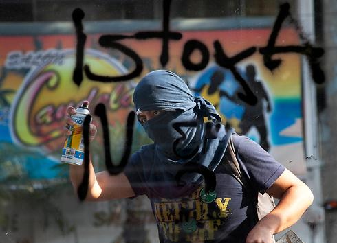 בחור צעיר מרסס כתובת גרפיטי על קיוסק במכסיקו סיטי במהלך צעדה לזכר טבח הסטודנטים בבירה ב-1971. מבצעי הטבח גויסו על ידי הממשלה המכסיקנית כדי לפזר את המחאה הפרו-דמוקרטית של הסטודנטים (צילום: AP) (צילום: AP)
