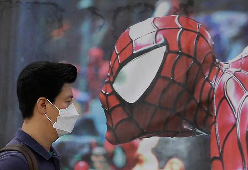 תושב סיאול חולף על פני פוסטר של ספיידרמן ומסכה על פניו על רקע התפרצות הנגיף MERS (תסמונת נשימתית מזרח תיכונית) בדרום קוריאה שכבר גבתה את חייהם של 14 בני אדם (צילום: AP) (צילום: AP)