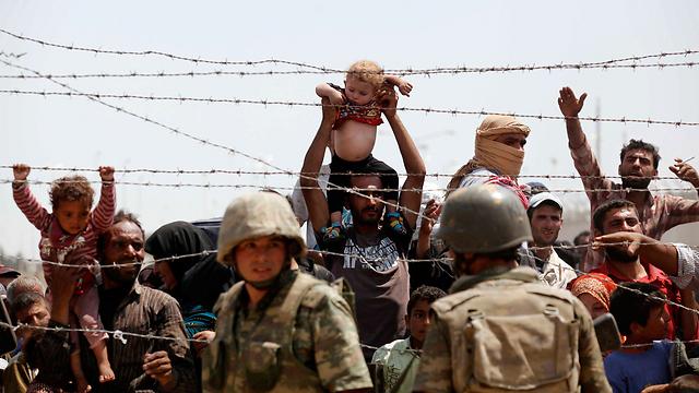 Syrian refugees crows the fence on the Turkish border. (Photo: EPA) (Photo: EPA)