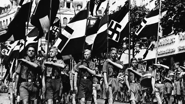 A group of boys march beneath Nazi standards in Berlin on February 24, 1936. Hitlerjugend members kept 'the fire of the revolution' burning (Photo: AP)