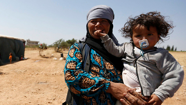 The Islamic State has created a refugee crisis in the Middle East. This woman and child fled from the group when they overtook Palmyra in Syria. (Photo: Reuters) (Photo: Reuters)