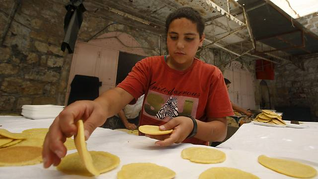 Palestinian Boy sorts Ramadan sweets in Hebron (Photo:Reuters)