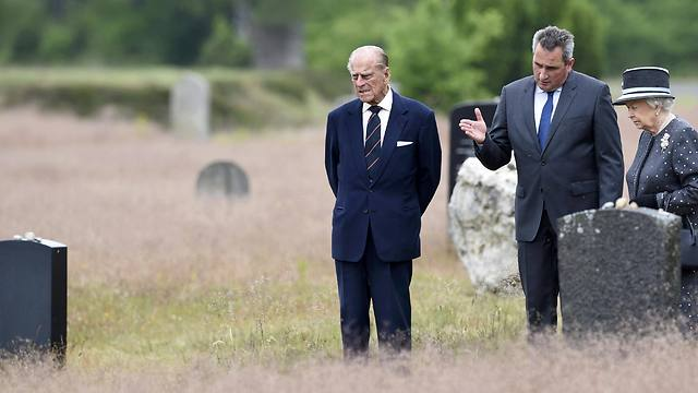 Queen Elizabeth II and Prince Philip listen to the director of the memorial Jens-Christian Wagner (Photo: EPA)