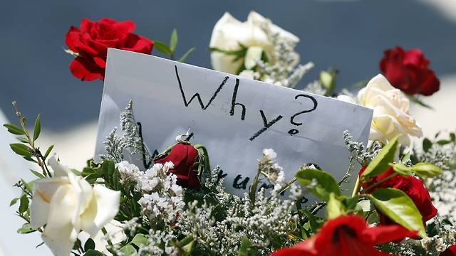 """""""למה?"""". פרחים בזירת הפיגוע (צילום: AP) (צילום: AP)"""