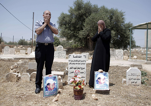Abu Khdeir's parents mourn at his grave (Photo: AFP)