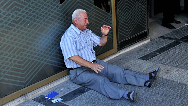חציפוטיאדיס ברגע הקשה מחוץ לבנק (צילום: AFP) (צילום: AFP)