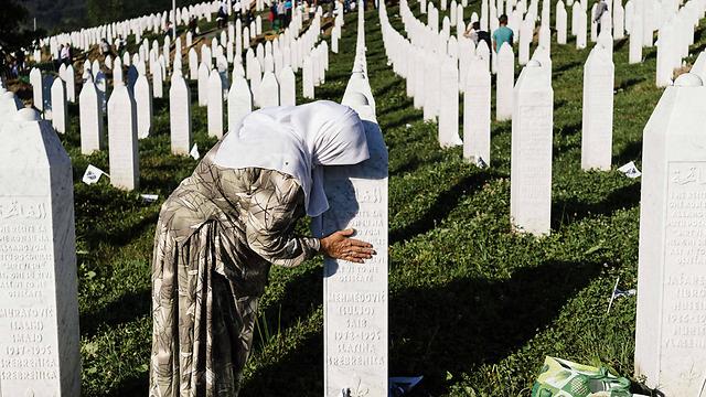 בוכים על קברי הנרצחים בסרברניצה (צילום: AFP) (צילום: AFP)