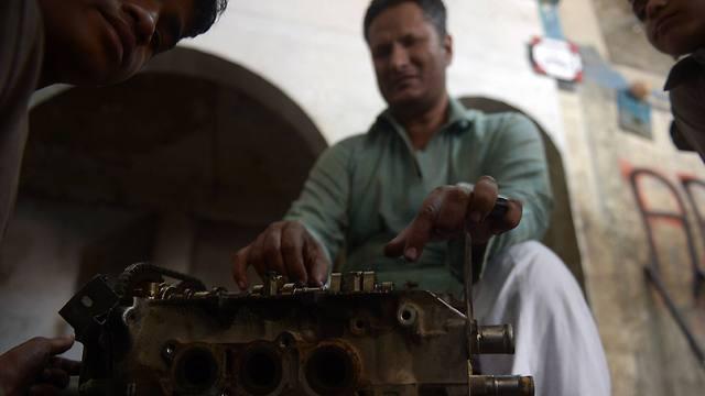 עסיף במוסך שלו בקראצ'י (צילום: AFP) (צילום: AFP)