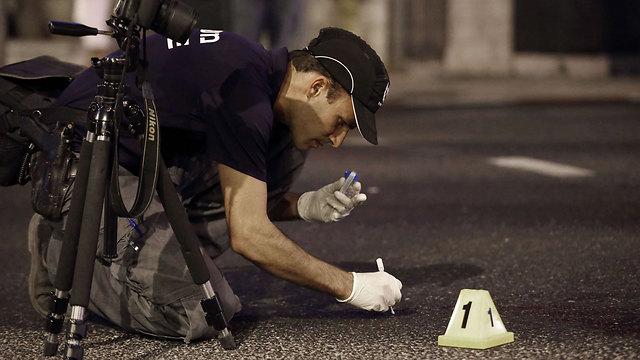 שוטר אוסף ממצאים בזירת הדקירה (צילום: AFP) (צילום: AFP)