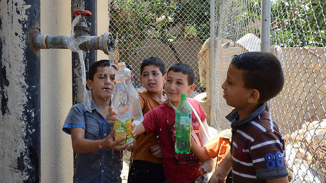Palestinian children getting water after supply was reduced in their village (Photo: Mohammad Shinawi)