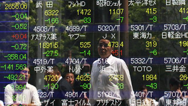 מביטים במסכים בטוקיו (צילום: EPA) (צילום: EPA)