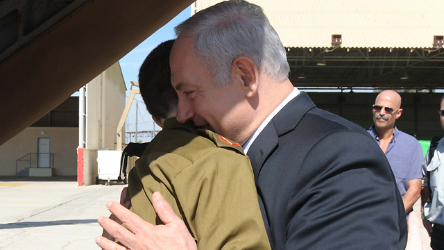 PM Netanyahu embracing Shalit on his release. The price paid for the soldier was too steep, Olmert said (Photo: GPO)