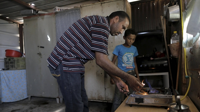 Nayef Zayed lights a gas burner running on methane produced in a HomeBioGas digester (Photo: Ammar Awad, Reuters)