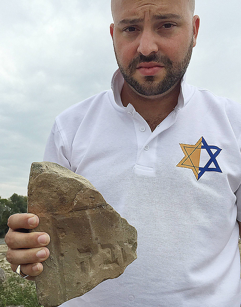 Jonny Daniels, the head of Jewish foundation 'From the Depths' displays tombstone fragment (Photo: AP)