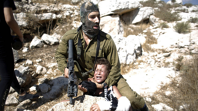 IDF soldier has Muhammad Tamini in headlock (Photo: Reuters)