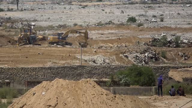 Palestinians sit and watch bulldozers and diggers work at the Egyptian side of the border with Gaza Strip (Photo: AP)
