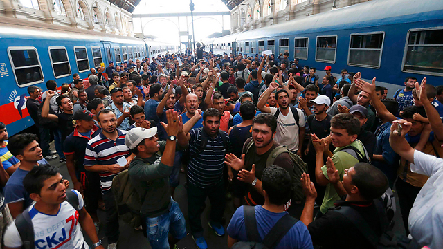 Refugees wait for a train to Germany in Budapest (Photo: Reuters)